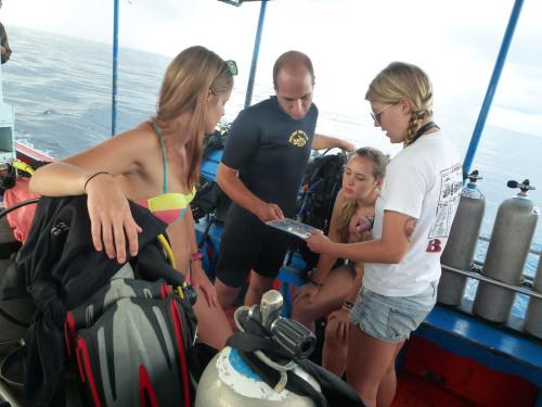 Revisando plano de mergulho com as instrutoras e vendo fotos dos peixes da região